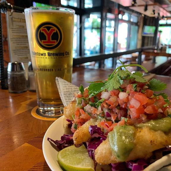 fish taco with salsa and pint of lager on table